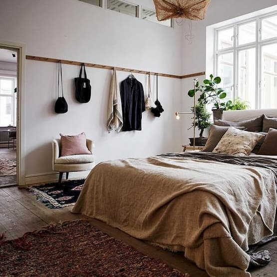 bedroom with brown pillows and bedding and with wood hook on the wall