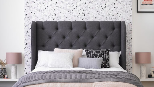 modern bedroom with black headboard different pillows and gray throw
