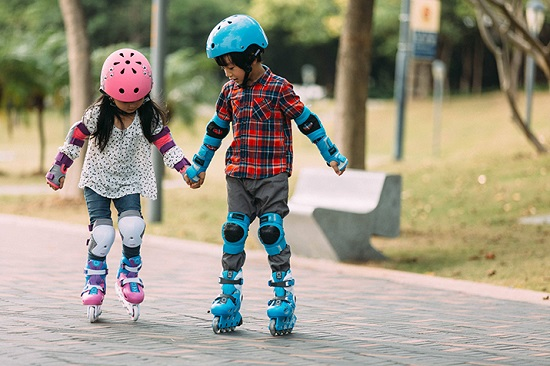 picture of two kids, a girl and a boy  roller skating in the park